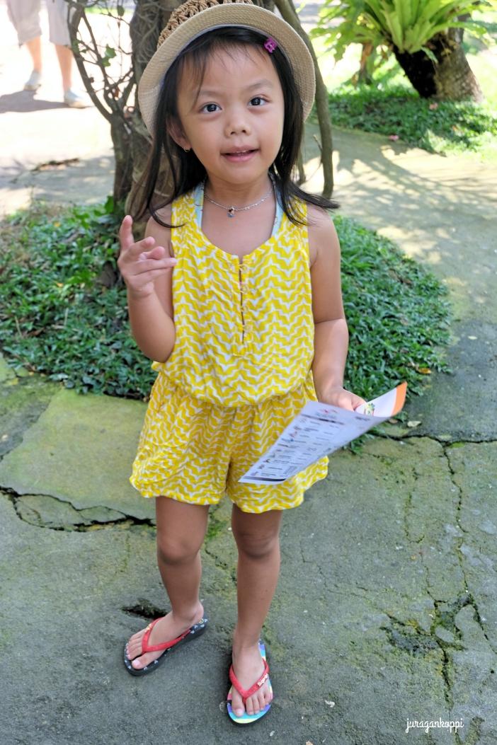 Anya nampak seperti Dora yang siap explore Bali Bird Park dengan peta di tangannya